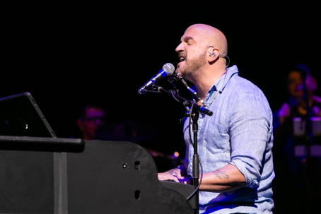 Performer Mike DelGuidice from the side singing while playing piano