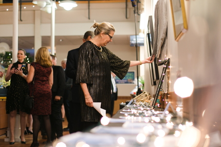 A woman looks at silent auction items displayed on long narrow tables with little white lights
